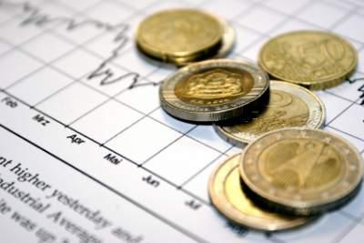 Plaatje van de beurskoersen met geldmunten op het papier.