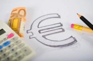 Vel papier met een getekend euro teken. Naast de tekening ligt een rekenmachine, potloden en een 50 euro biljet.